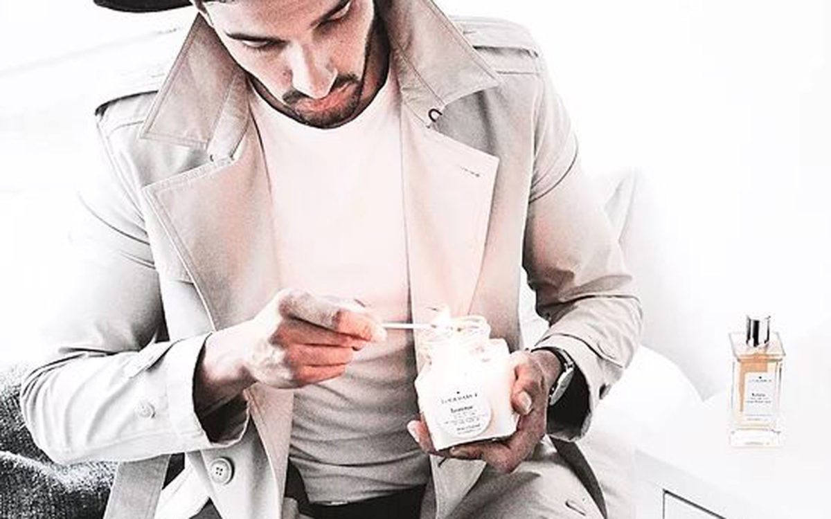 Good looking man lighting a Lola Darcy Candle